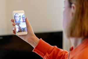 A woman in a group video chat on her smartphone.