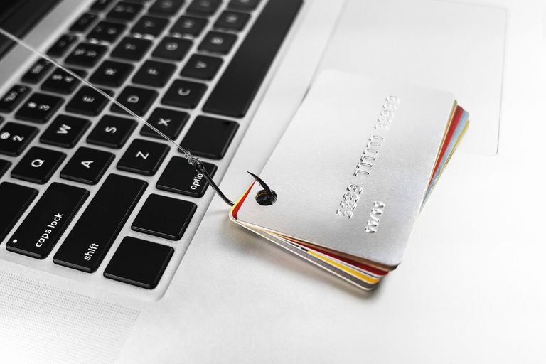 A stack of credit cards sitting on a laptop, getting hooked by a fishing hook that's coming from the laptop's monitor.