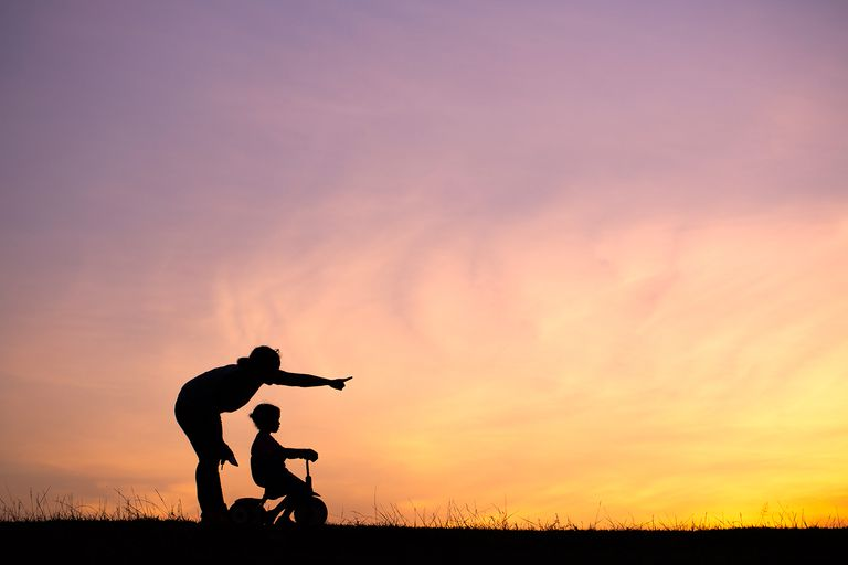Silhouette Woman With Daughter Riding Bicycle On Field Against Orange Sky