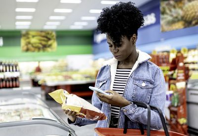 A woman scanning a barcode with her iPhone in a grocery store.
