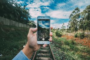 Hand holding iPhone in front of railroad tracks
