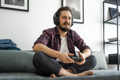 A man sitting on a couch holding a games controller