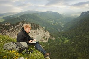 Man using laptop on remote cliff's edge