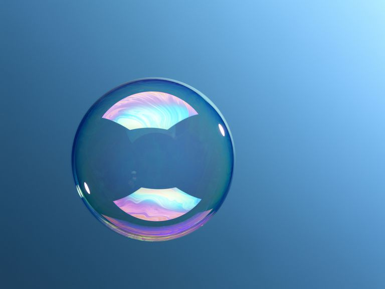 A bubble floating in front of a blue backdrop