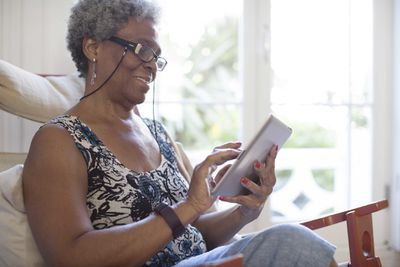 A smiling older woman browsing an iPad while sitting on a sofa.