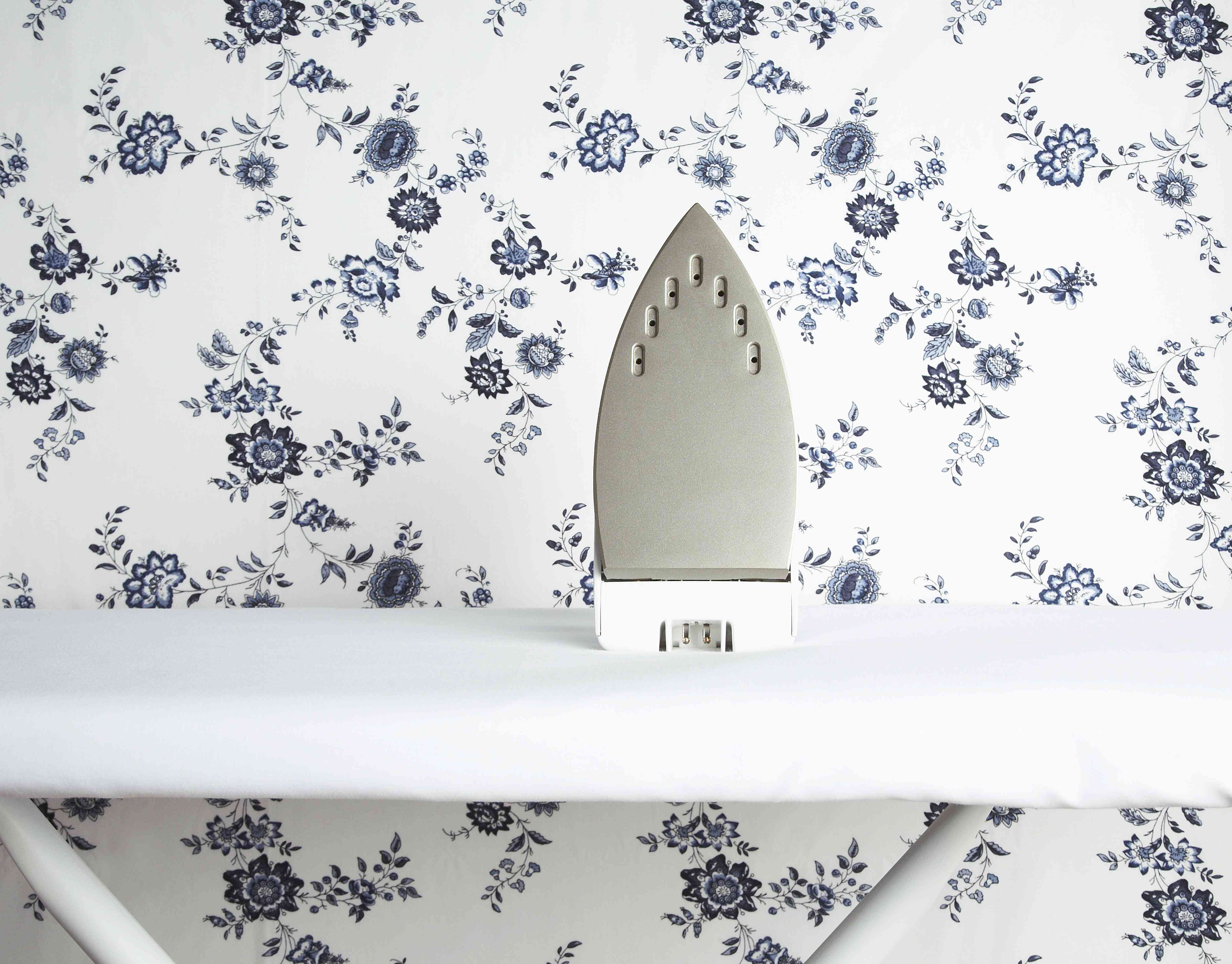 Iron on ironing board with wallpaper pattern in background