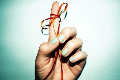 A hand with a string tied around a finger, representing a reminder for something