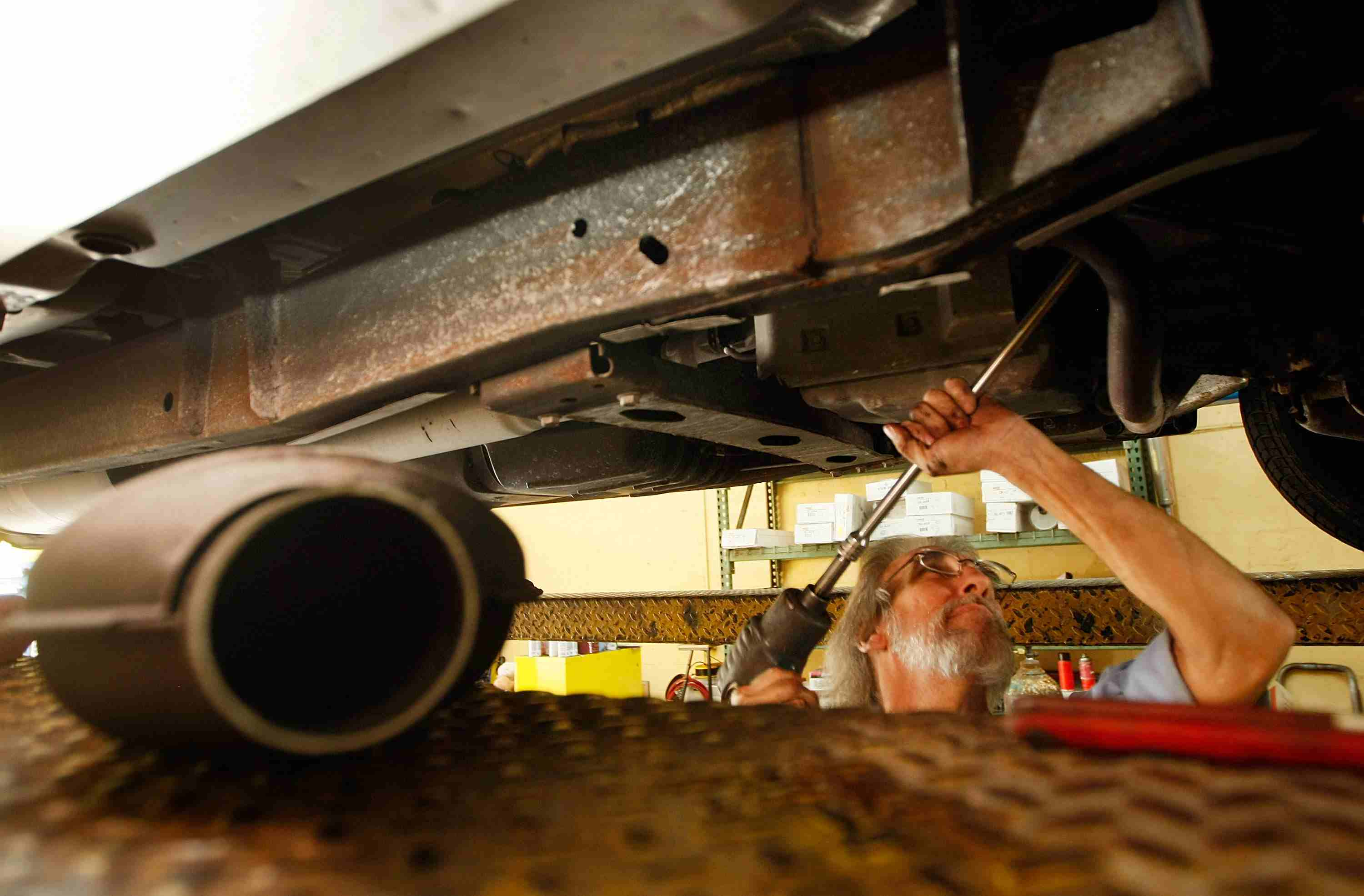 A mechanic removes a plugged catalytic converter.