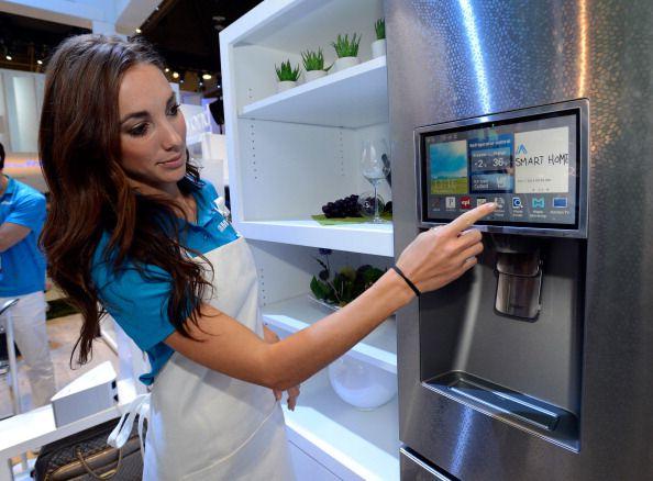 A woman touching a screen on a smart fridge