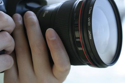 A DSLR camera with a 77mm UV lens filter on the front of the lens.