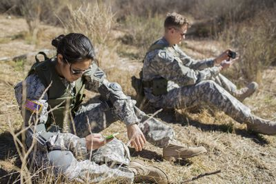 Two active duty military members using their phones in the field.