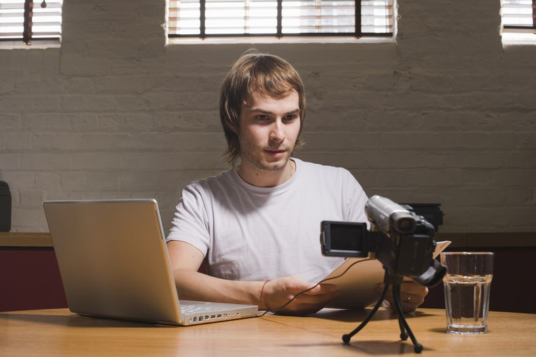 Young man with laptop reading to digital video camera