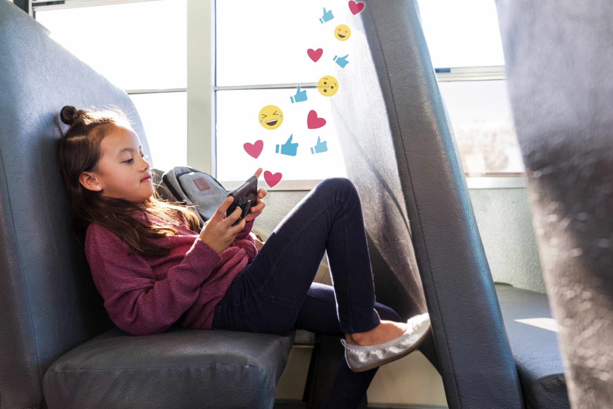 A child on a school bus looking at social media on a smartphone.