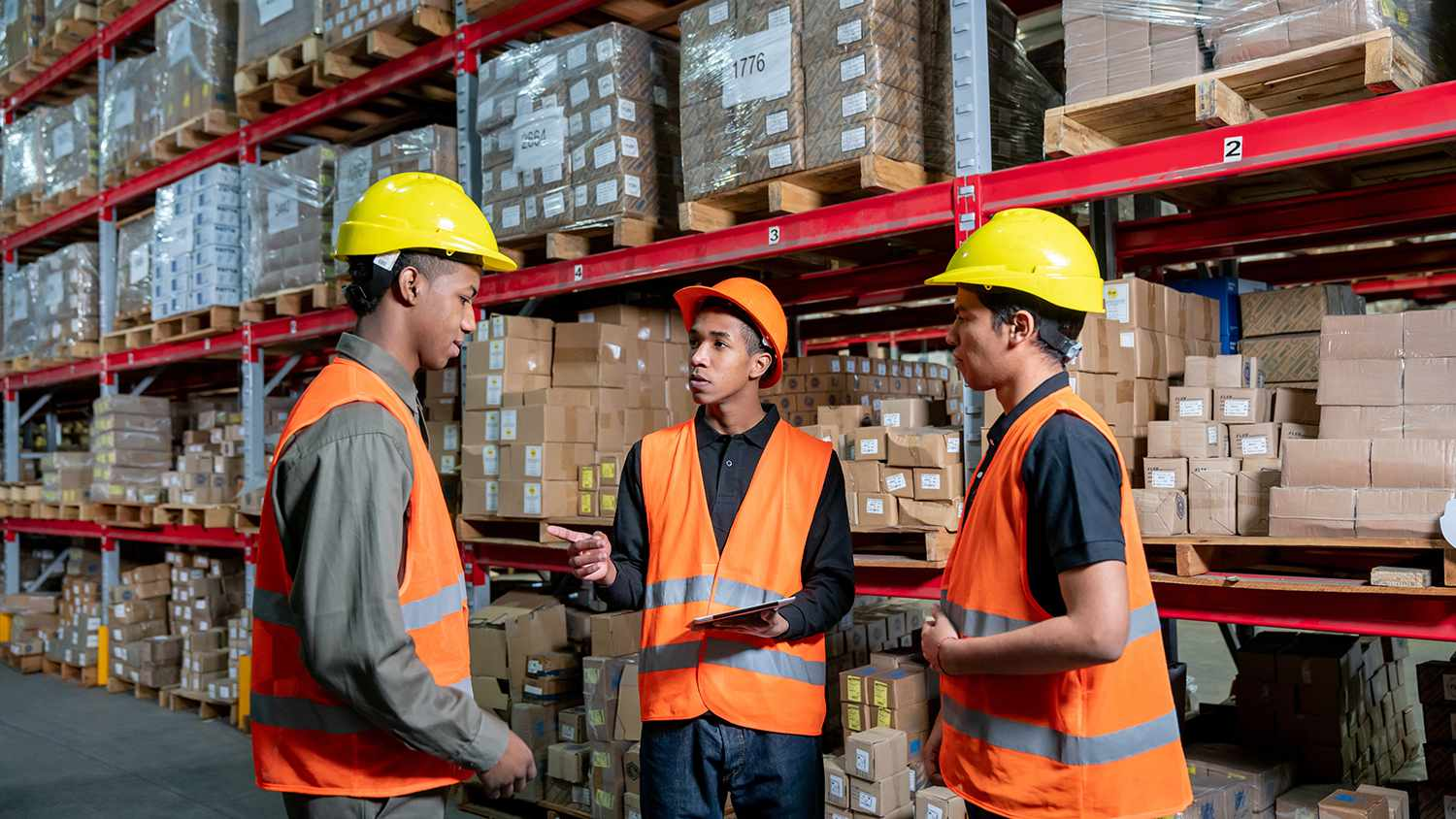 Young supervisor assigning tasks to his team at a warehouse