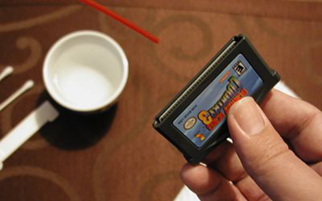 Cleaning a Gameboy cartridge with compressed air.