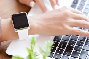 Hand wearable apple watch typing on laptop