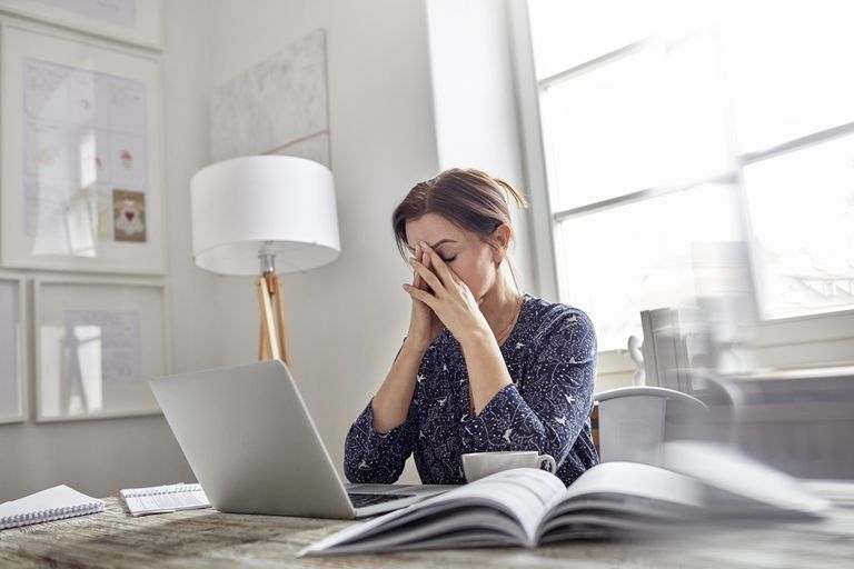 A frustrated woman using a Mac notebook computer.