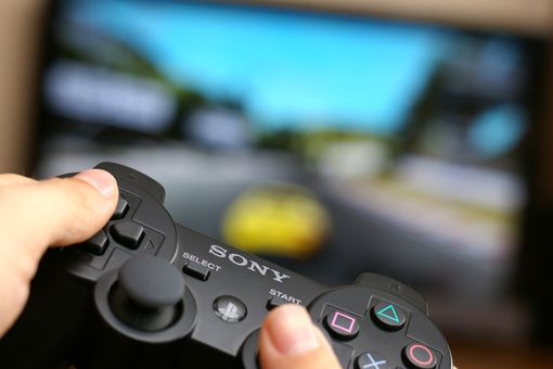 Man holding Sony Dualshock wireless controller while playing Gran Turismo 5 on Playstation 3.