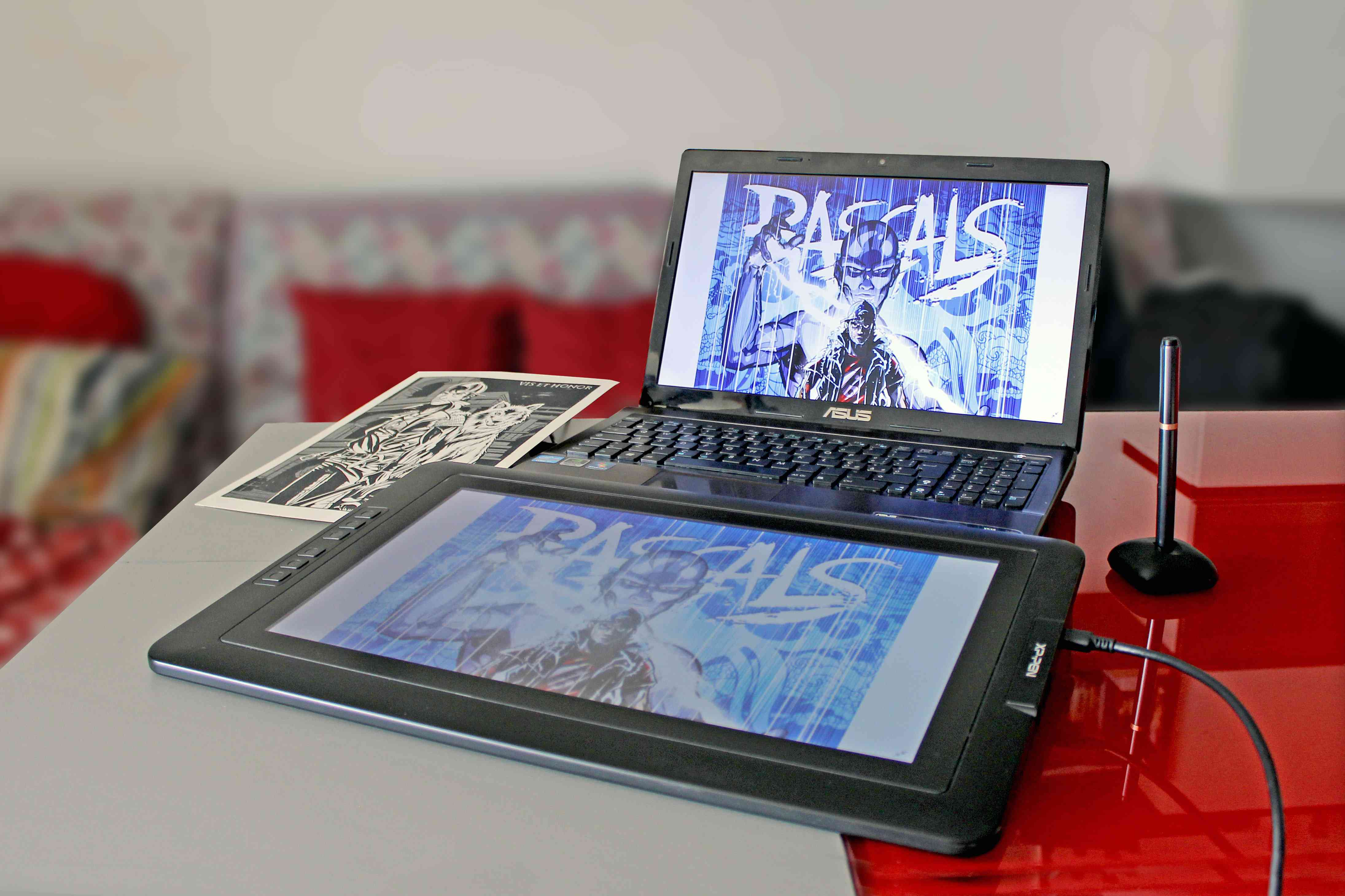 A drawing tablet connected to an Asus computer with a pen in the holder next to it.