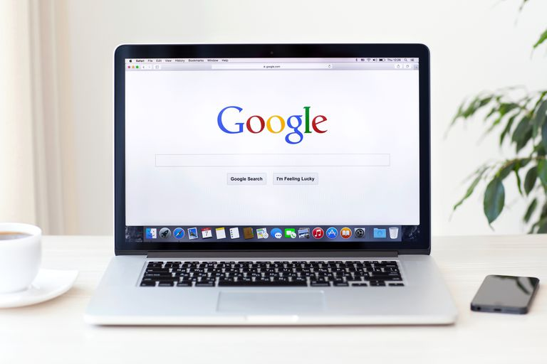 An image of a Macbook with a browser open showing the Google homepage.