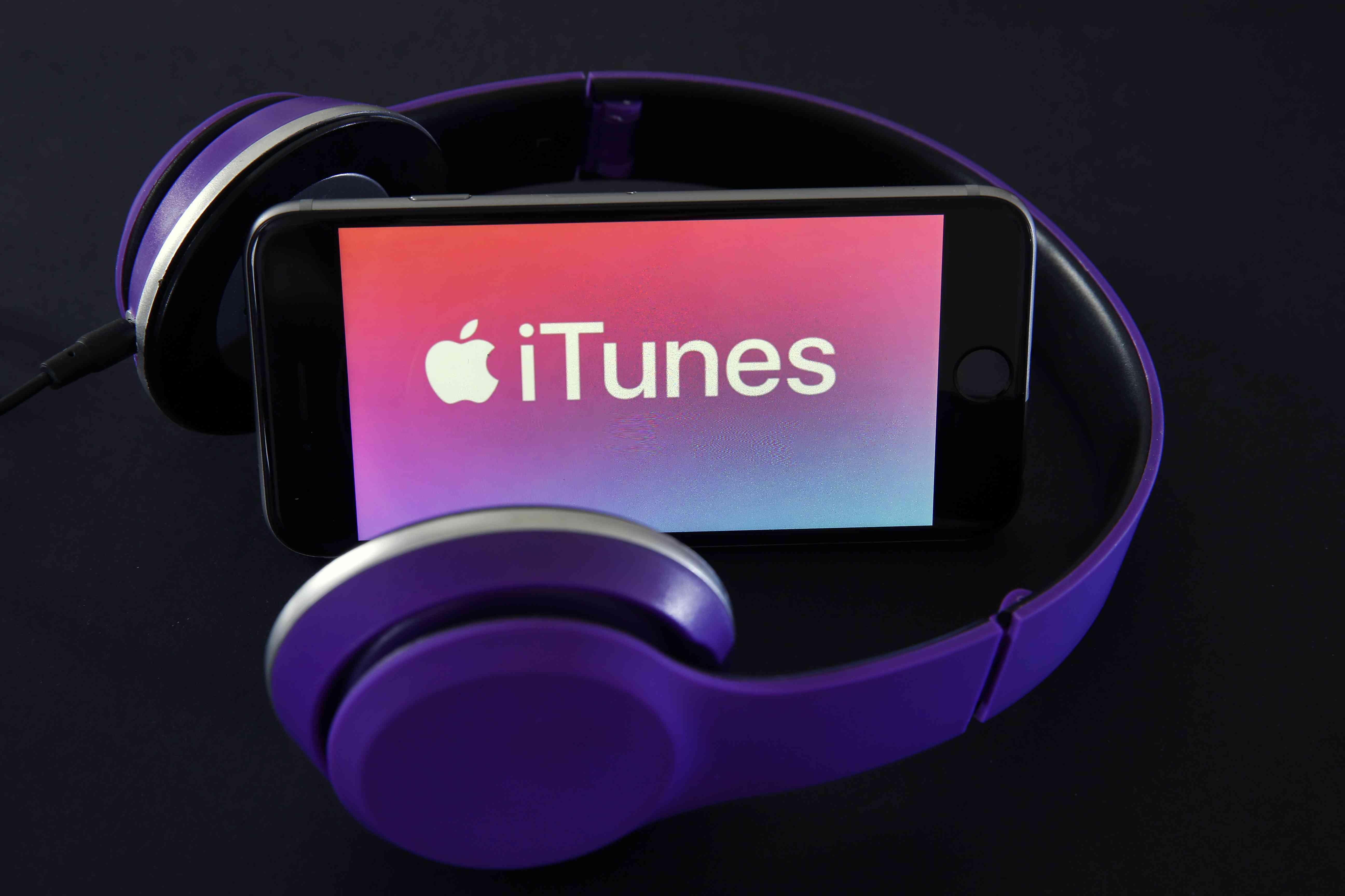 Headphones surrounding iPhone showing iTunes music download service logo on screen