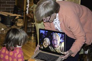 Grandparents talking to grandchild using laptop camera