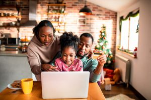 A family of three gathering around a laptop on a kitchen table
