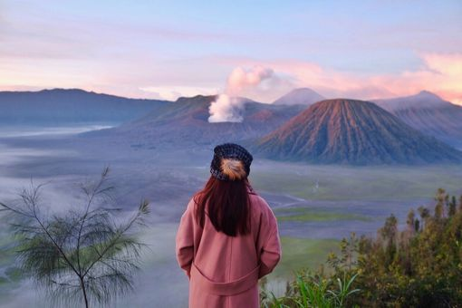 A woman staring at a smoking volcano in the distance.