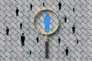 Magnifying glass highlighting a person icon in a group of people icons.