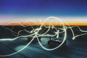 Picture of white light beams on a rooftop at night