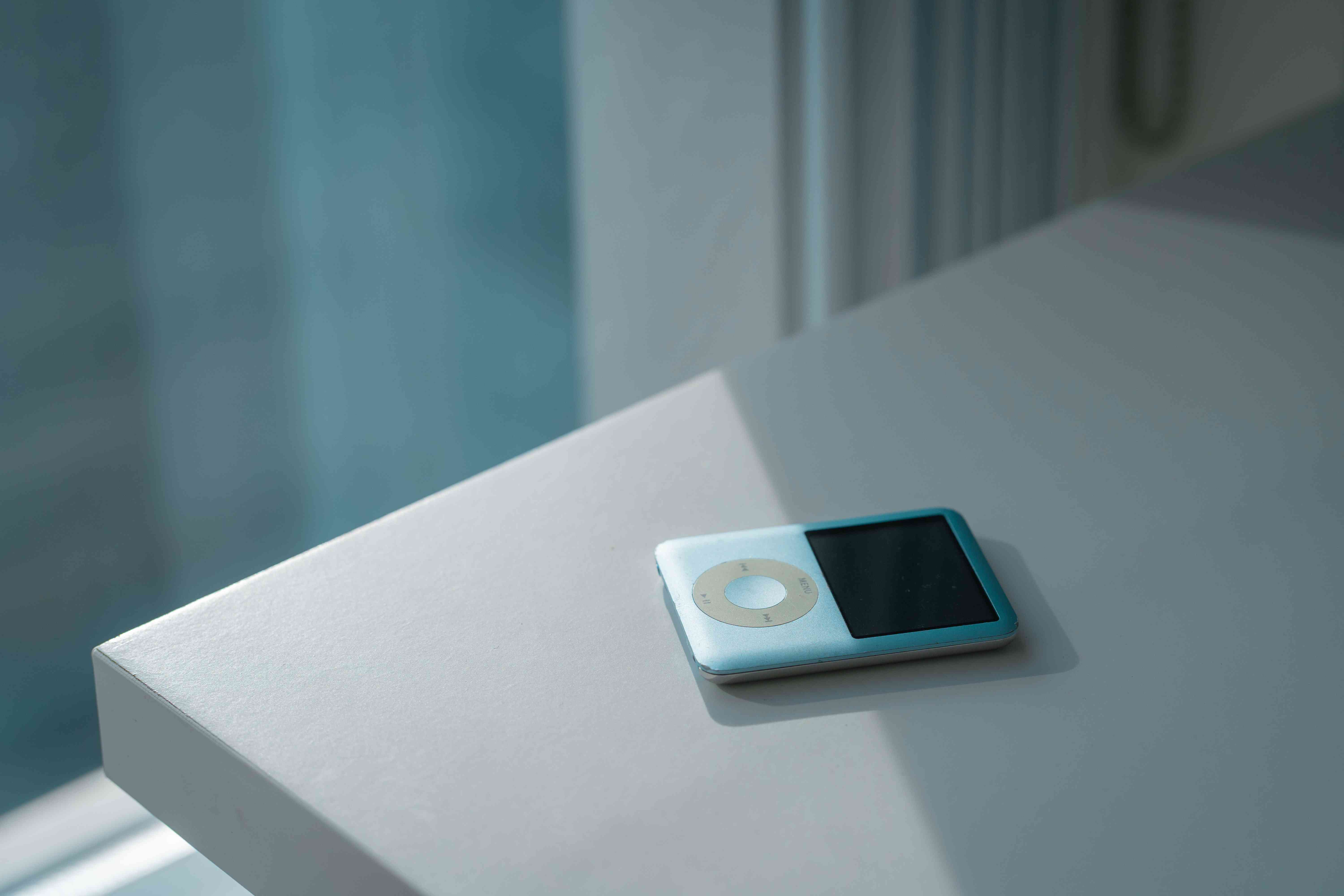 Teal iPod Classic sitting at the edge of a counter.