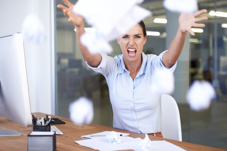 Stressed employee throwing papers