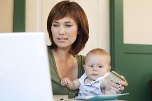 A woman at a laptop screen holding a baby and a credit card