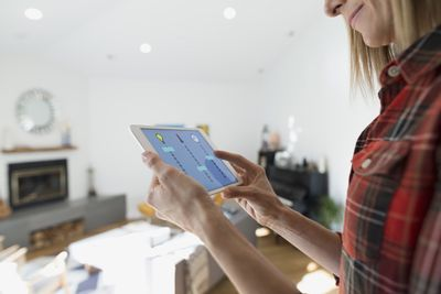 Woman controlling home utilities with digital tablet