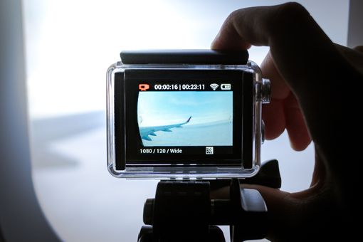 An action camera filming on an airplane