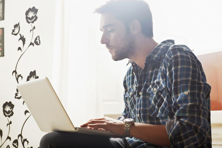 Young man sitting indoor using laptop computer