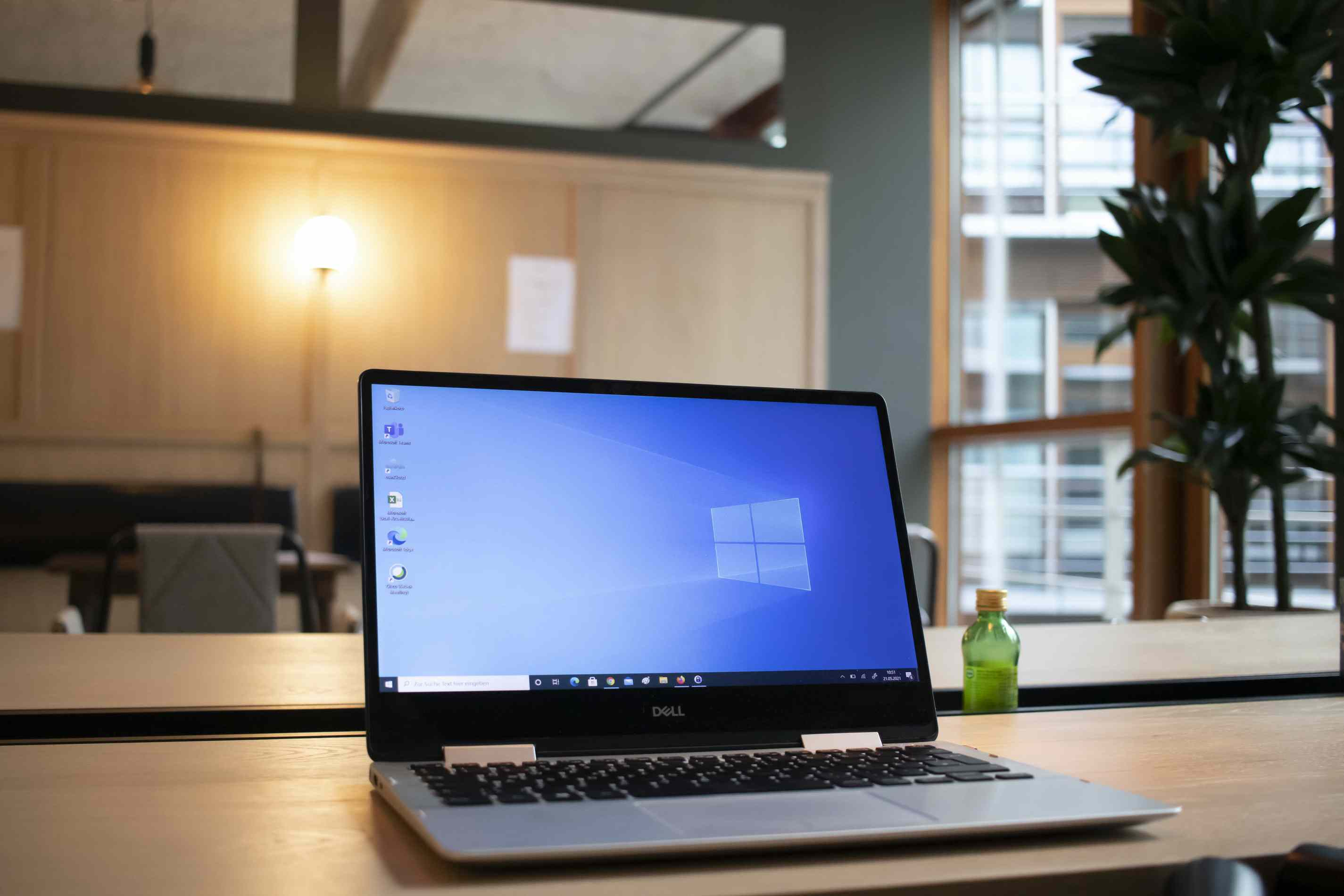 Windows laptop resting on a wooden conference table