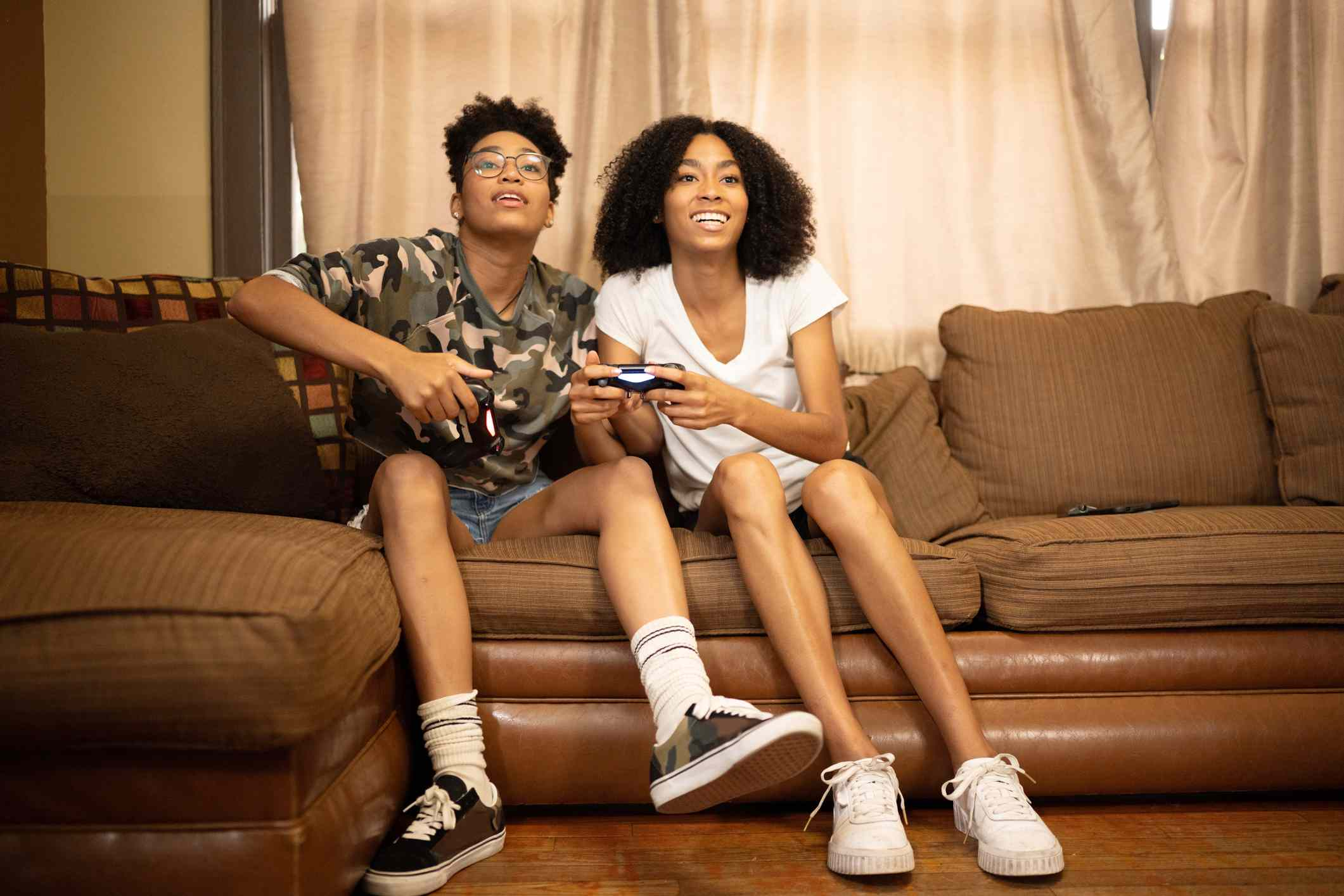 Two teenagers playing video games at home while sitting on a couch.