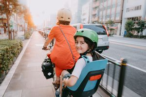 A parent cycling with a child on a bike lane in the city.