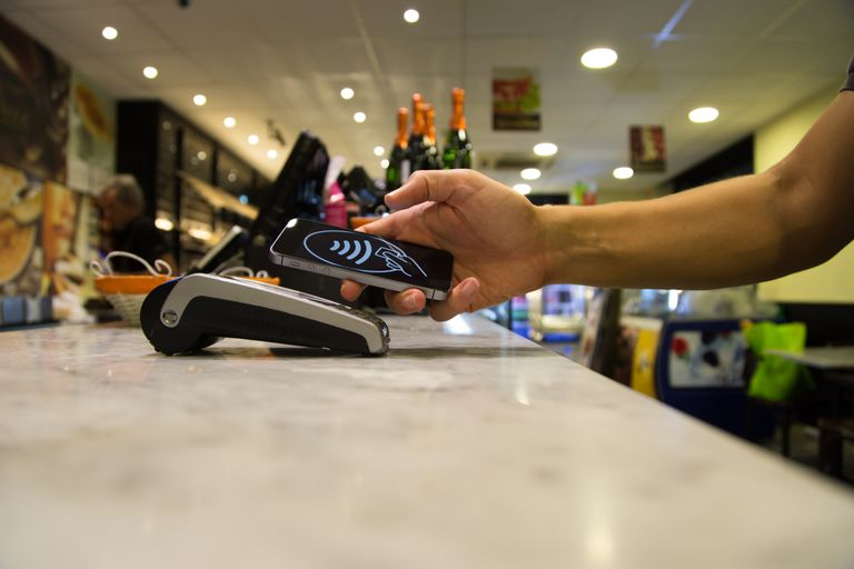 Person using mobile pay on their phone for a purchase