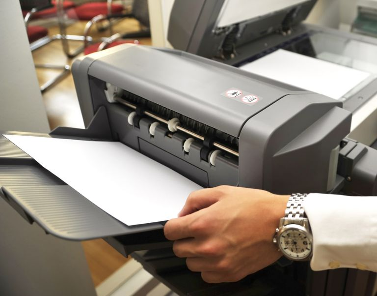 Hand taking a printed page out of a printer