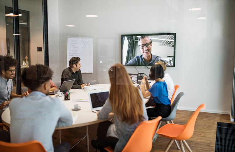 Team video conferencing with remote workers in an office.