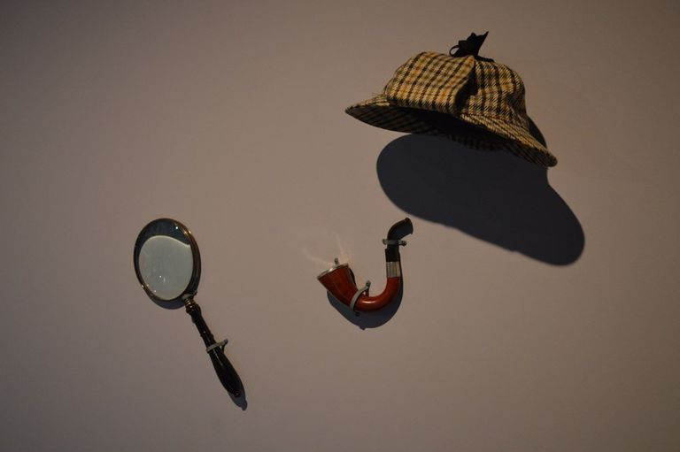 A magnifying glass, pipe, and floppy cap in reference to Sherlock Holmes