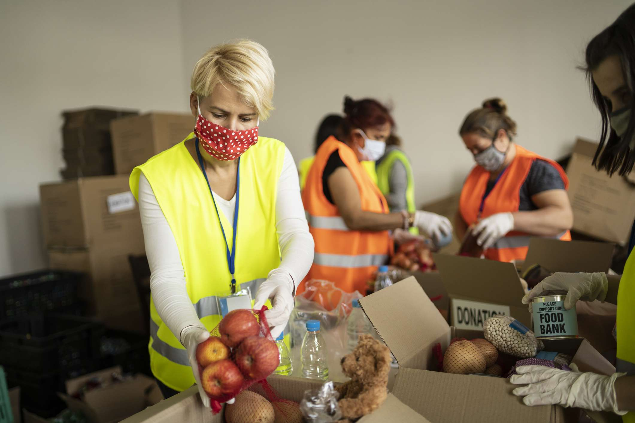 People wearing protective masks and gloves working in a food bank.