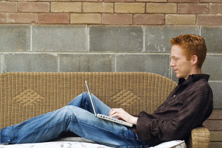 Man with laptop reclining on sofa