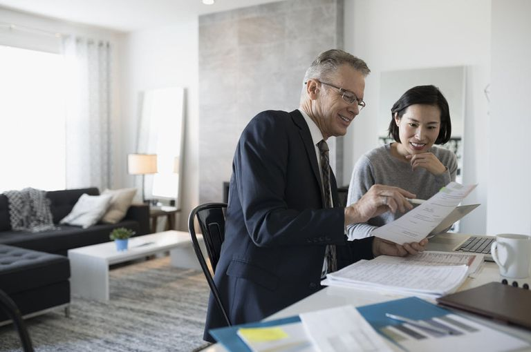 Male accountant discussing average financial analysis with Asian female in the living room.