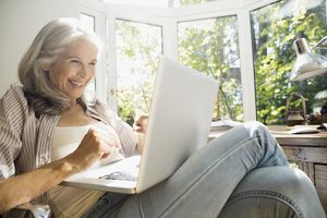 Person using laptop in sunny home office