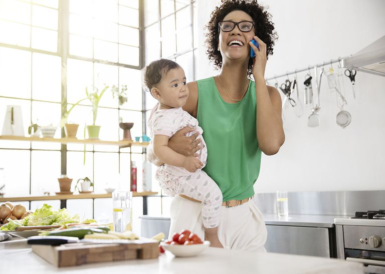 woman on the phone holding a baby