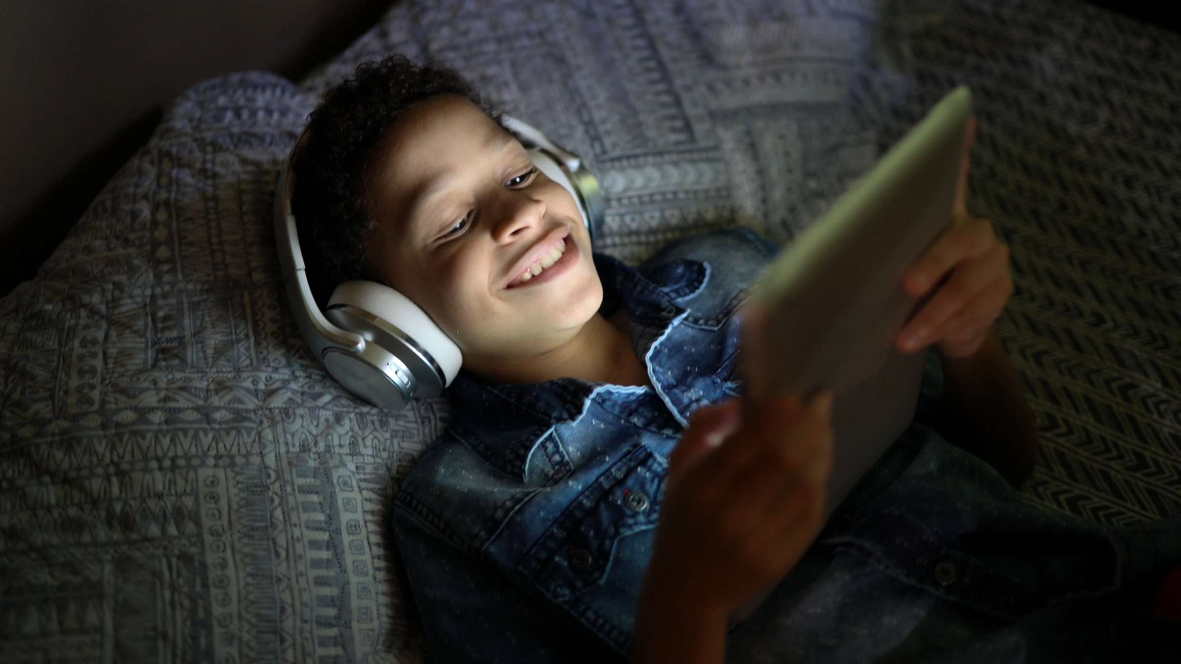 A teen laying in bed watching a movie on a tablet.