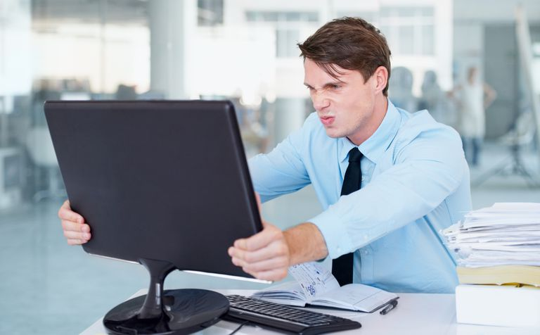 A businessman angrily gripping his computer screen.